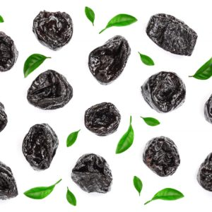 Dried Plum Prunes Decorated With Green Leaves Isolated On A White Background. Top View. Flat Lay
