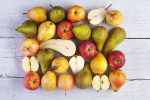 Apples And Pears Whole And Halved Shot From Above On White Wooden Boards