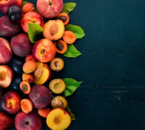 Fresh Fruits. Apricot, Peach, Plums, Nectarines. On A Wooden Background. Top View. Free Space For Your Text.